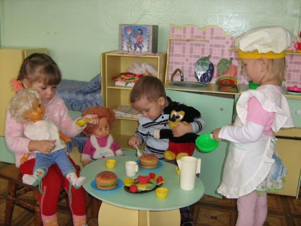 Две девочки и мальчик играют в чаепитие