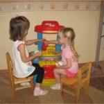 Две девочки играют с большой детской кухней