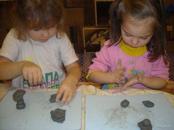 Две девочки лепят из глины