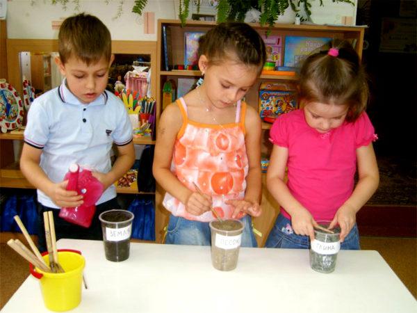 Трое детей проводят эксперименты с песком, землёй, водой и глиной