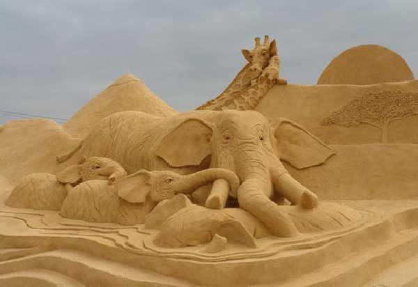 Фигуры слонов и жирафов из песка