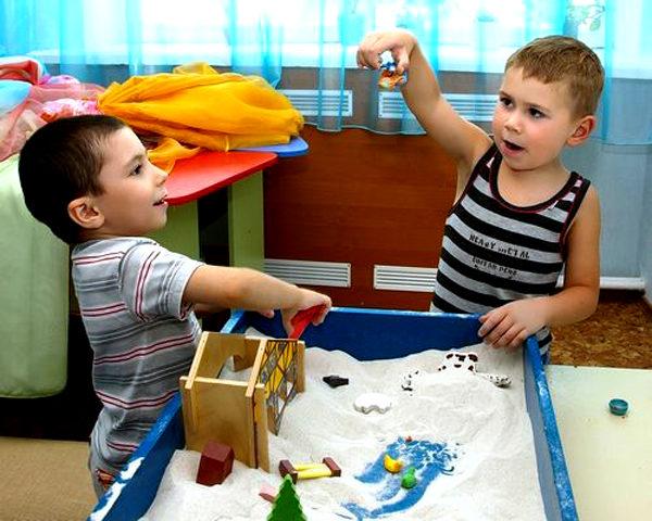 Два мальчика играют в юнгианской песочнице в группе