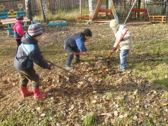 Дети граблями сгребают листья на садовом участке