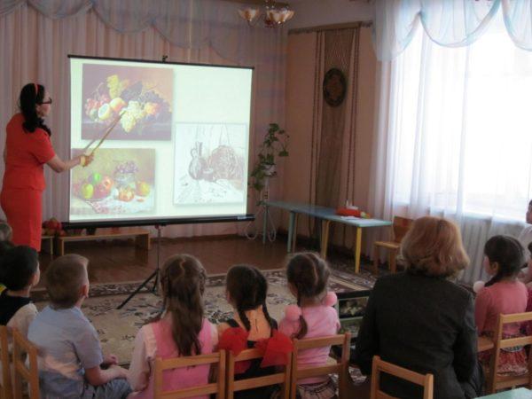 Педагог показывает детям репродукции картин на большом экране