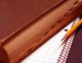 Книга в коричневом переплёте лежит на блокноте, рядом простой карандаш