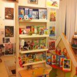 Стеллаж с книгами и игрушками, рядом размещены иллюстрации известных сказок