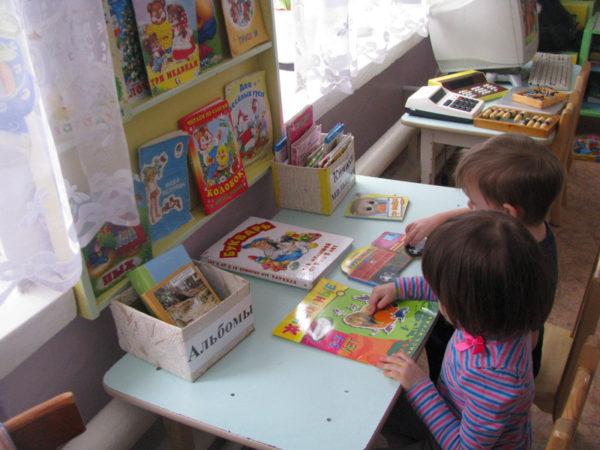 Мальчик и девочка рассматривают книги в уголке чтения