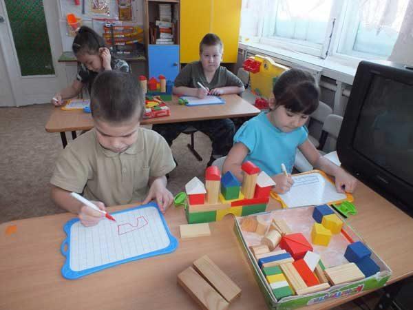 Дети, сидя за партами, занимаются конструированием из строительных материалов