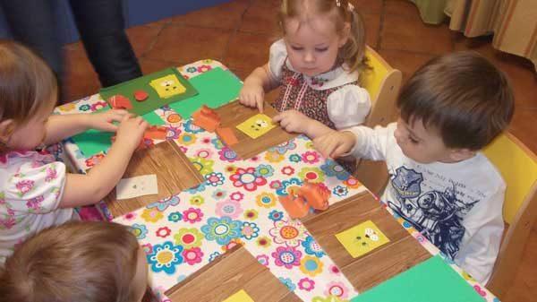 Малыши сидят за столами и занимаются конструированием из ткани
