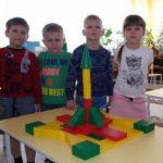 Четыре ребёнка стоят рядом с построенной из конструктора ракетой