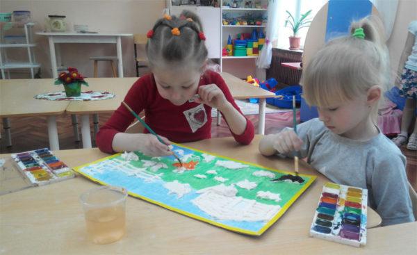 Две девочки раскрашивают красками общий рисунок