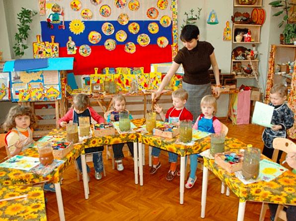 Дети рисуют в кружке художественно-эстетического развития, воспитатель помогает