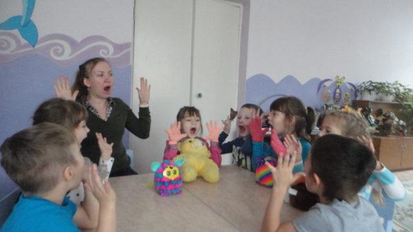 Логопед делает с детьми, сидящими полукругом за столом, дыхательную гимнастику