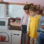 Трое детей стоят рядом с макетом-декорацией для спектакля «Русская печь»