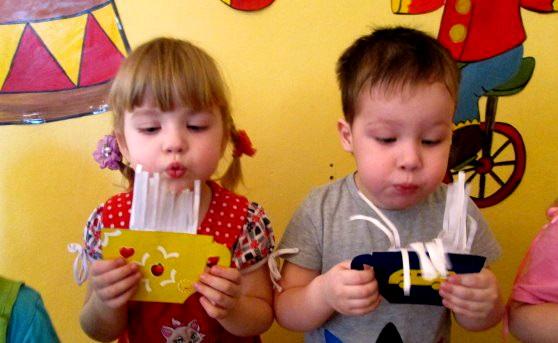 Мальчик и девочка дуют на поделки из бумаги