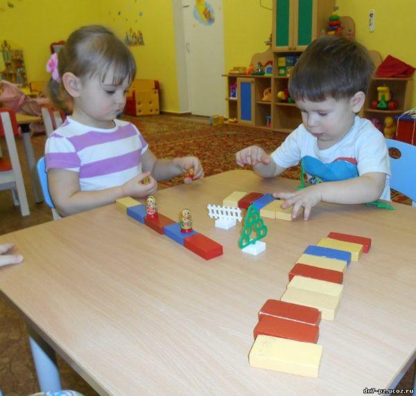 Мальчик и девочка, сидя за столом, делают дорожки из деревянных кирпичиков