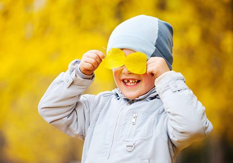 Улыбающийся мальчик закрыл глаза жёлтыми листьями