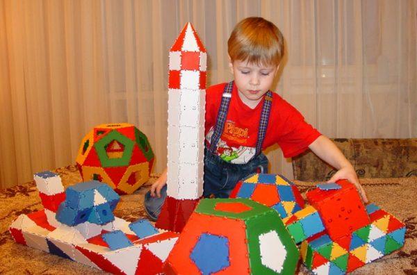 Мальчик играет с ракетой, кораблём и шарами из крупного конструктора