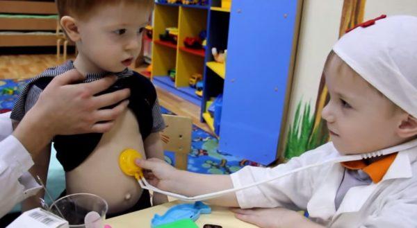 Мальчик в костюме доктора фонендоскопом слушает другого мальчика