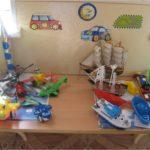 Модели летающего и идущего по морю транспорта на столе, картинки-машинки на стене