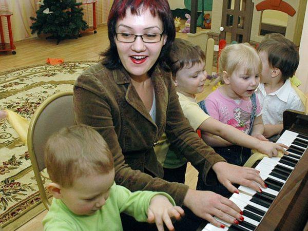 Музыкальный руководитель играет на фортепиано в окружении трёх мальчиков и девочки