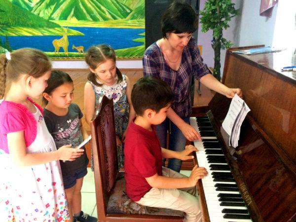 Мальчик сидит за фортепиано, воспитатель и трое детей стоят рядом