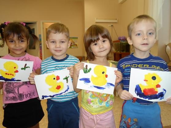 Четверо детей держат в руках рисунки уточек