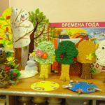 Объёмные поделки-деревья на столе, на заднем фоне плакат «Времена года»