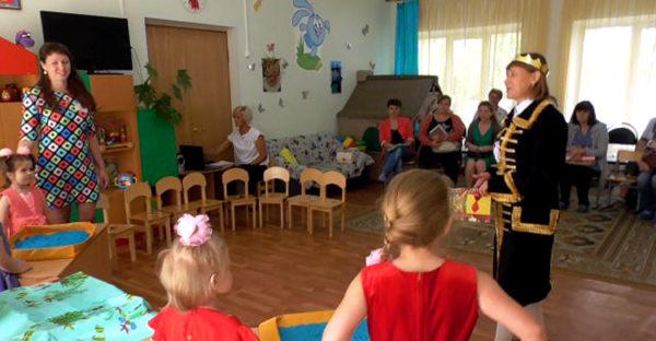 Педагог в костюме королевы выступает перед детьми и родителями