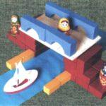 Мостик, построенный из строительного материала, с матрёшками на нём
