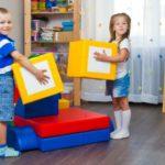 Мальчик и девочка занимаются моделированием из крупных блоков
