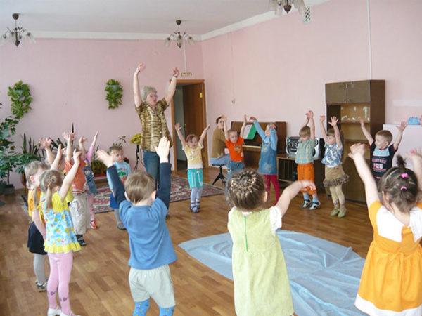 Дети и воспитатель стоят в кругу, подняв руки вверх