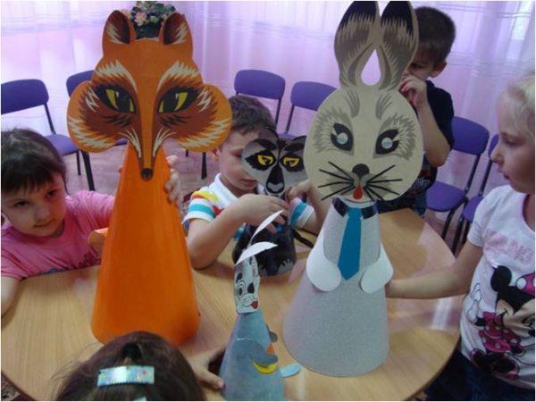На столе стоят бумажные куклы животных, дети рассматривают их