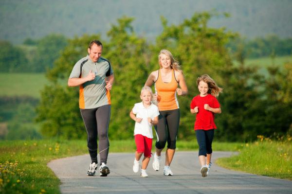 Папа, мама и двое детей бегут по загородной дороге