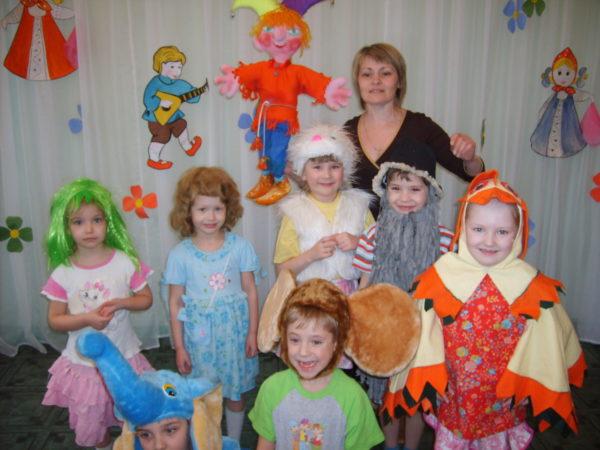 Педагог и дети в костюмах стоят на сцене