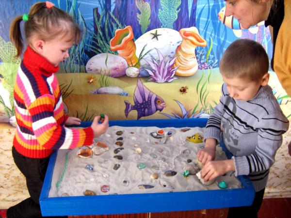 Мальчик и девочка играют в песочнице с ракушками и другими мелкими предметами