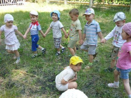 Дети идут, держась за руки, по траве, один мальчик сидит на корточках