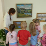 Дети и воспитатель на выставке картин