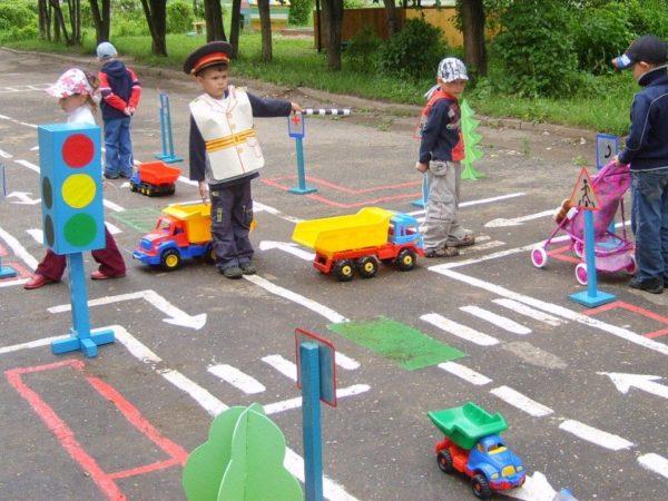 Дети играют с машинками на площадке с дорожными знаками и светофорами
