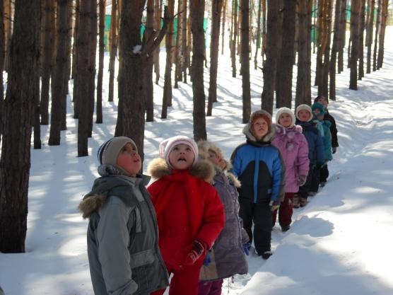 Дети идут по заснеженной тропинке в парке