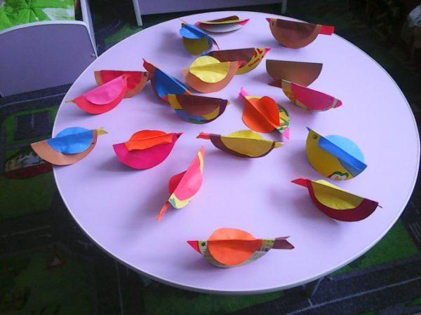 Яркие птички из бумаги на столе