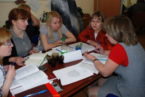 Пятеро воспитателей сидят за столом с разложенными на нём документами