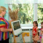Дети рассматривают репродукцию картины, воспитатель стоит у доски