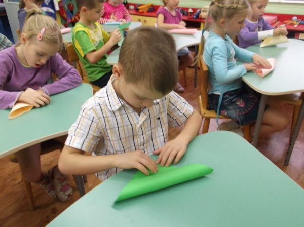 Дети, сидя за партами, занимаются конструированием из бумаги