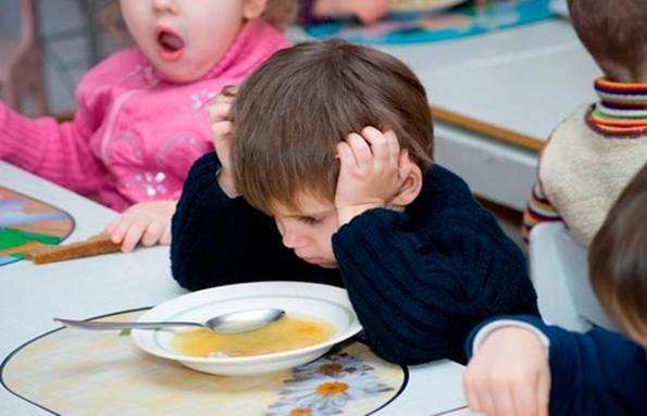 Перед мальчиком стоит тарелка супа, он не хочет есть