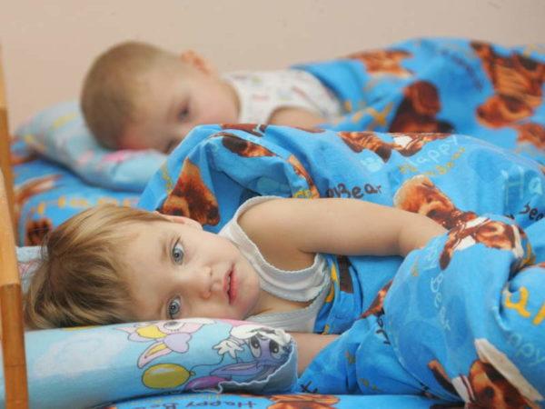 Два ребёнка не спят, лёжа в кровати, во время тихого часа