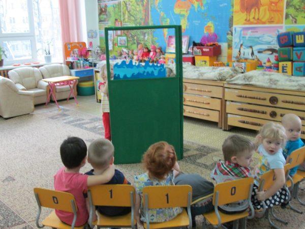 Ребёнок за ширмой с изображением моря, остальные малыши сидят на стульях полукругом