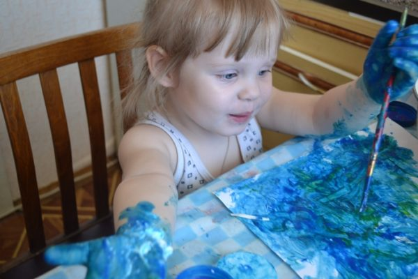 Девочка рисует синей краской