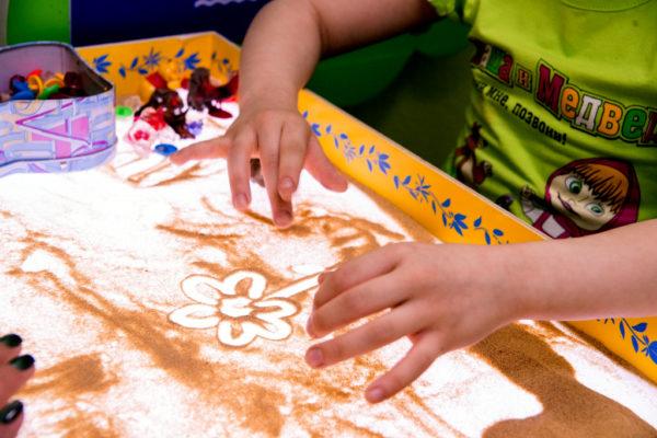 Ребёнок рисует песком на специальной доске