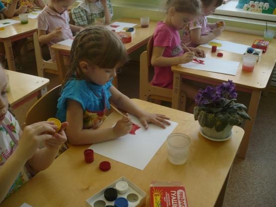 Дети, сидя за партами, рисуют гуашью